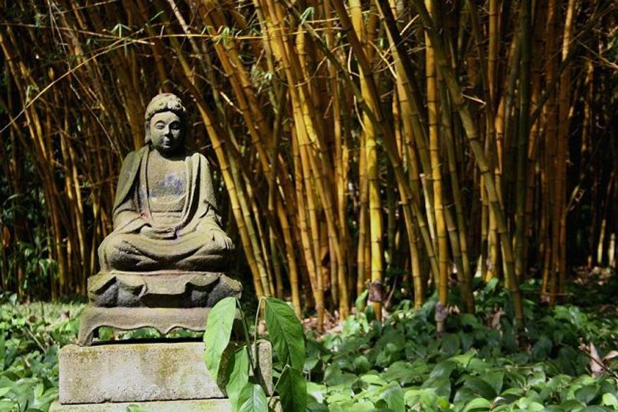 ** FILE ** An image of Buddha sits amid bamboo at the Allerton Garden on Kauai, Hawaii.