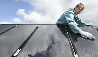 Heiko Schuster, development engineer of the solar technology company Sulfurcell cleaned solar panels atop the company's headquarters in Berlin. The Algerian government's solar energy project is in its early stage and faces daunting financial and technological obstacles.