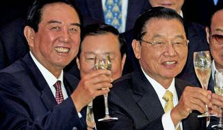 **FILE** Chen Yunlin (left), head of Beijing's Association for Relations Across the Taiwan Strait, and Chiang Pin-kung, Taiwan's chief negotiator, toast the charter flight and tourism agreement. (Associated Press)