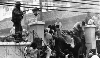 Above: Mobs scale the wall of the U.S. Embassy in Saigon, Vietnam, in April 1975 to escape the imminent communist takeover. Left: In April 1956, black and white passengers sit segregated on a trolley in Atlanta, despite a Supreme Court decision. Both were pivot points in U.S. history.