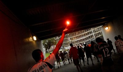 A D.C. United fan who identified himself only as A.J. Hooligan with the group La Barra Brava lights the way with a road flare as the crowd marches to the stadium from the parking lot, as the D.C. United hosts the New York Red Bulls at RFK Stadium in Washington D.C., Saturday, June 14, 2008. (Rod Lamkey Jr./The Washington Times)