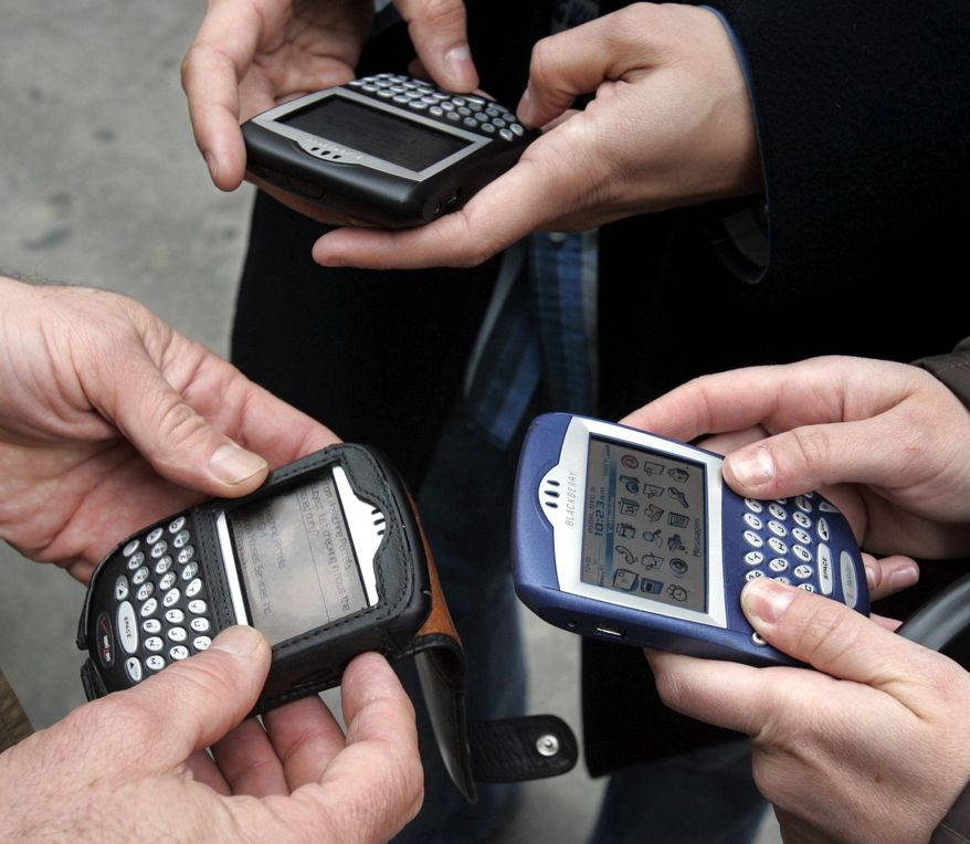 **FILE** Three people use BlackBerry devices in New York's Times Square on Dec. 5, 2005. (Associated Press)