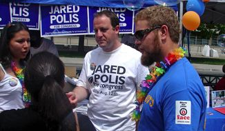 Democratic congressional candidate Jared Polis (center) discusses the issues with attendees at Denver's recent gay pride festival. Mr. Polis is running in Colorado's 2nd District. (Valerie Richardson/The Washington Times)