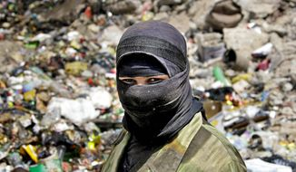 ** FILE ** A woman sifting through trash at a garbage dump in Baghdad's Shi'ite stronghold of Sadr City wears a head scarf and veil. Women in Iraq are under more pressure to conform to Islamic traditions that strictly limit their rights and opportunities. (Associated Press)