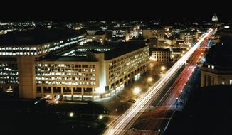 The J. Edgar Hoover Building, which opened to employees in 1974, dominates the nighttime cityscape on Pennyslvania Avenue NW. ** FILE **