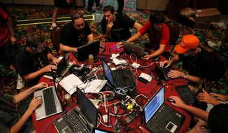 "** FILE ** In this 2008 file photo, participants compete in the ""Capture the Flag"" hacking competition, a highlight of the DefCon conference in Las Vegas. After qualifying before the conference, teams battle to seize and keep control of a network set up for the game. (Associated Press)"