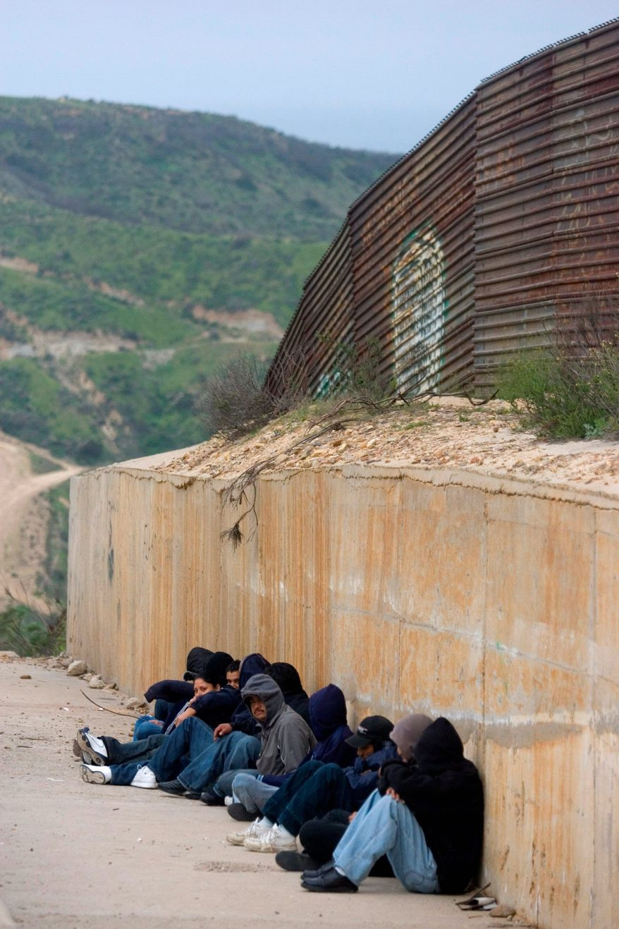 **FILE** People wait for nightfall on Mexico's side of the U.S.-Mexico border fence. (Associated Press)