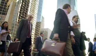 With the Sears Tower behind them, pedestrians head away from their offices in downtown Chicago, Tuesday morning, Sept. 11, 2001, in Chicago. Many Chicago buildings, including the Sears Tower, were shut down as security measures in response to the attack at the World Trade Center in New York.(AP Photo/M. Spencer Green)
