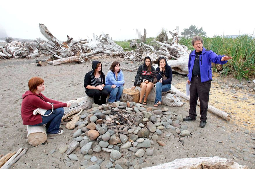"""** ADVANCE FOR SUNDAY, SEPT. 21 ** Visitors listen Friday, Sept. 5, 2008, to Michael Gurling, right, of the Forks, Wash., Chamber of Commerce, talk about the bonfire location on a beach in LaPush, Wash., that is portrayed as the place where Bella Swan, the main character in author Stephenie Meyer's vampire-themed """"Twilight"""" books, learns that her high-school friend Edward Cullen is really a vampire. The visitors were taking part in a """"Twilight Tour"""" led by Gurling that takes fans of the books, which are set in the nearby town of Forks, Wash., around to locations central to the plot and characters. The attention is welcome in Forks, which has long suffered by the decline in the timber industry. (AP Photo/Ted S. Warren)"""