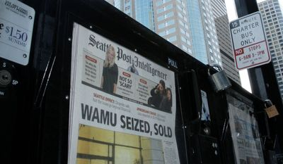 A newspaper box near the Washington Mutual Tower in downtown Seattle displays editions of the Seattle Post-Intelligencer with a front-page story on the bank's seizure and sale.**FILE**Associated Press