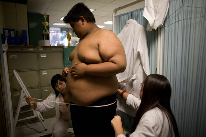 ** FILE ** Jesus Alberto Garcia, who is 14 and weighs 310 pounds, gets a checkup at Mexico's Children's Hospital. (Associated Press)