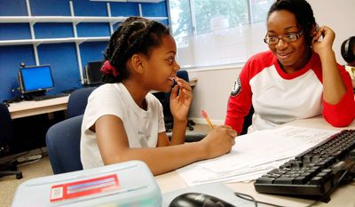 AmeriCorps member Samantha Royes (right) helps Fayvin Bowens, 11, a student at Noyes Elementary School, with her homework at the Youth Gateway Program, an initiative of the Community Preservation and Development Corps., in Washington D.C., Friday, Oct. 10, 2008. (Rod Lamkey Jr./The Washington Times)