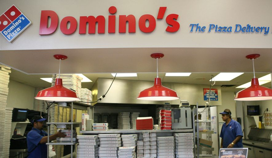 Sohel islar left and malak khan work behind the counter for Dominos pizza salon