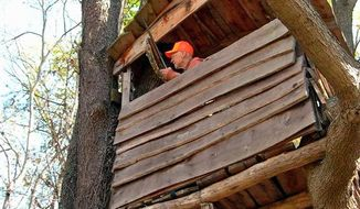 **FILE** A hunter in a deer stand wears a fluorescent orange cap.