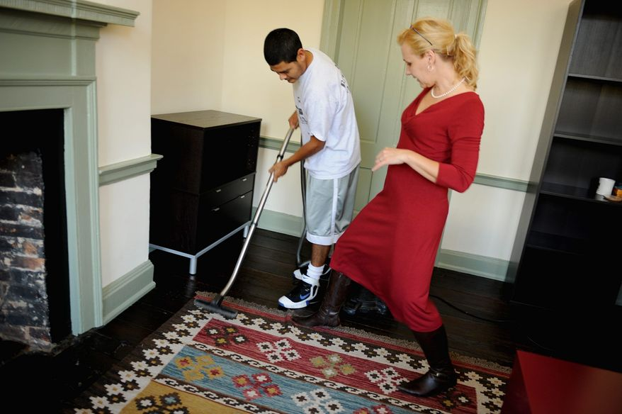 **FILE** Pernilla Alex, owner of Mrs. Lavender Inc. and EcoCrew, an environmentally friendly cleaning service, holds down the edge of a throw rug as Alvaro Ruiz vacuums in the offices of Livingston Communications in Alexandria, Va. (Barbara Salisbury/The Washington Times)