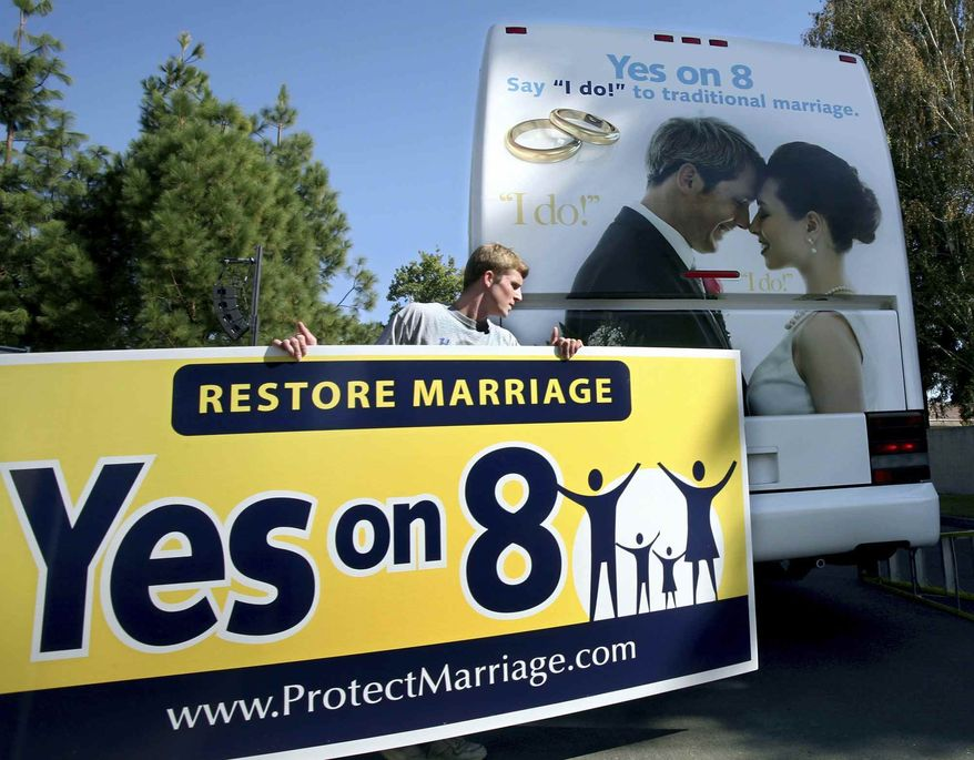 Richie Beanan from Los Angeles, puts a sign on a bus that will tour California in support of Proposition 8. after a rally in Sacramento, Calif., on Monday, Oct. 20, 2008. If passed Proposition 8 would amend the California state constitution to ban same sex marriage.