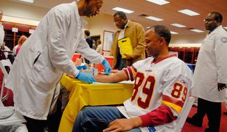 Calvin Franklin, 44, takes blood for a prostate-specific antigen test from Army veteran Trent Riley, 41, of Hanover, Md., in the Redskins' locker room Saturday during a team-hosted health screening. (Mary F. Calvert/The Washington Times)