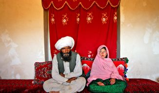 ** FILE ** Soon-to-be-wed Faiz Mohammed (left), 40, and Ghulam Haider, 11, are pictured at her home in a rural village of Damarda in Afghanistan's Ghor province in 2008. (Stephanie Sinclair/Special to The Washington Times)
