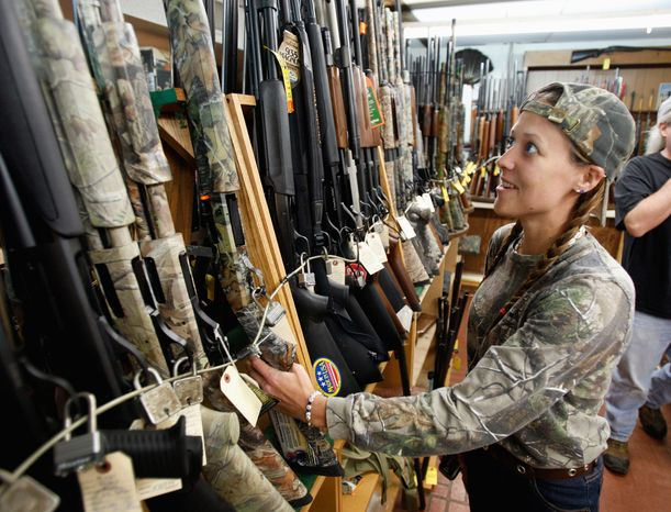 Rachel Smith, 32, of Richmond, looks over shotguns at the Bob Moates sport shop in Richmond, Va., on Thursday. Smith, the mother of five children and an avid hunter plans to purchase several guns before President-elect Obama takes office. (Associated Press)
