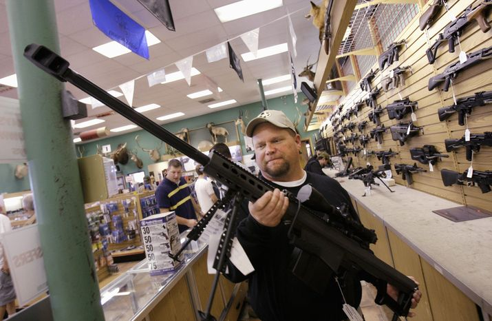 ** FILE ** Curtis Irwin holds a .50 caliber rifle to show at a gun shop in Fort Worth, Texas, on Thursday. The Cheaper Than Dirt gun store recorded a record day of gun sales the day after the election of President-elect Barack Obama and is since having trouble keeping up with the demand for assault rifles. (Associated Press)
