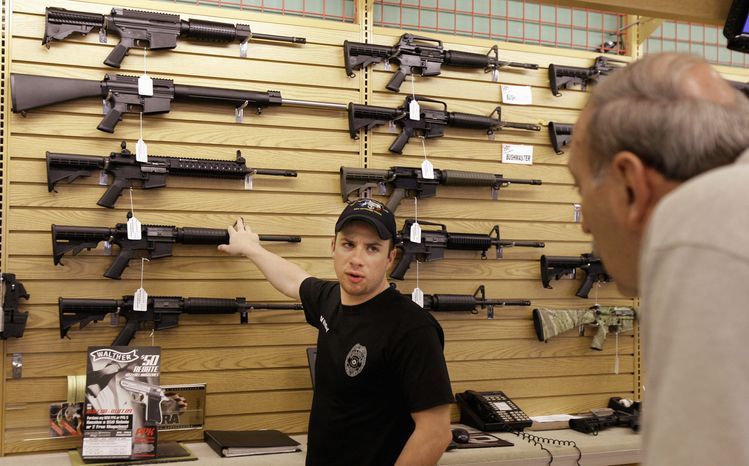** FILE ** Case Vermillion answers a customer's question at a gun shop in Fort Worth, Texas, on in 2008. (Associated Press)