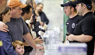 Customers line up to look at firearms at a gun shop in Fort Worth, Texas, Thursday, Nov. 6, 2008. The Cheaper Than Dirt gun store recorded a record day of gun sales the day after the election of President-elect Barack Obama and is having trouble keeping up with the demand for assault riffles. (Associated Press)