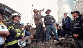Then-President Bush speaks to rescue workers, firefighters and police officers from the rubble of ground zero in New York City three days after the attacks on Sept. 11, 2001. Retired firefighter Bob Beckwith and then-New York Gov. George Pataki join the president. (Getty Images) ** FILE **