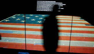 A museum visitor walks by the new Star-Spangled Banner exhibit, showcasing the nearly 200-year-old flag that inspired the writing of the song that became America's national anthem.