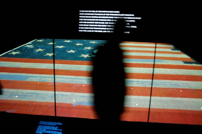 A museum visitor walks by the new Star-Spangled Banner exhibit, showcasing the nearly 200-year-old fla