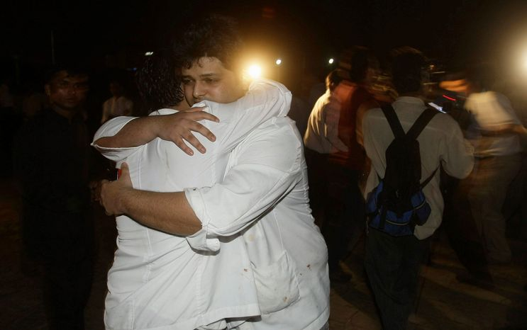 Taj Mahal hotel employees comfort each other after being rescued. A group calling itself the Deccan Mujahideen claimed responsibility for the attacks. (Associated Press)