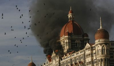 ** FILE ** Pigeons fly as the Taj Mahal Palace hotel continued to burn in Mumbai, India, on Thursday, Nov. 27, 2008. Teams of heavily armed gunmen stormed luxury hotels, a popular restaurant, hospitals and a crowded train station in coordinated attacks across India's financial capital, police said. (AP Photo)
