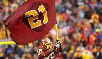 **FILE** Washington Redskins' Clinton Portis carries a flag bearing the number of slain fellow player Sean Taylor as the Washington Redskins host the New York Giants at FedEx Field in Landover, Md., Sunday.