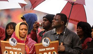 Pedro Taylor (right) Donna Junor, parents of Sean Taylor endure emotions and rain during a pre-game ceremony on behalf of their son.(Michael Connor / The Washington Times)