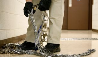A U.S. Immigration and Customs Enforcement officer prepares handcuffs and leg irons before a prisoner transfer. (Associated Press/File)