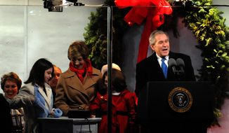 ** FILE ** As his eight-year presidency nears the end, President George W. Bush and first lady Laura Bush are joined by two unidentified girls as they light the National Christmas Tree. (Rod Lamkey Jr./ The Washington Times)