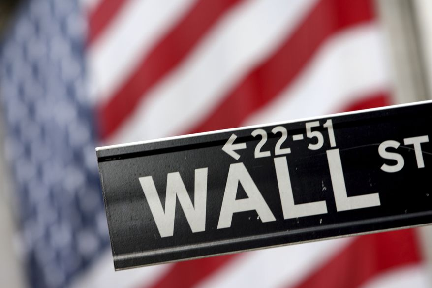 ** FILE ** A Wall Street street sign is pictured in front of the American flag hanging on the New York Stock Exchange in New York. (AP Photo/Mary Altaffer)