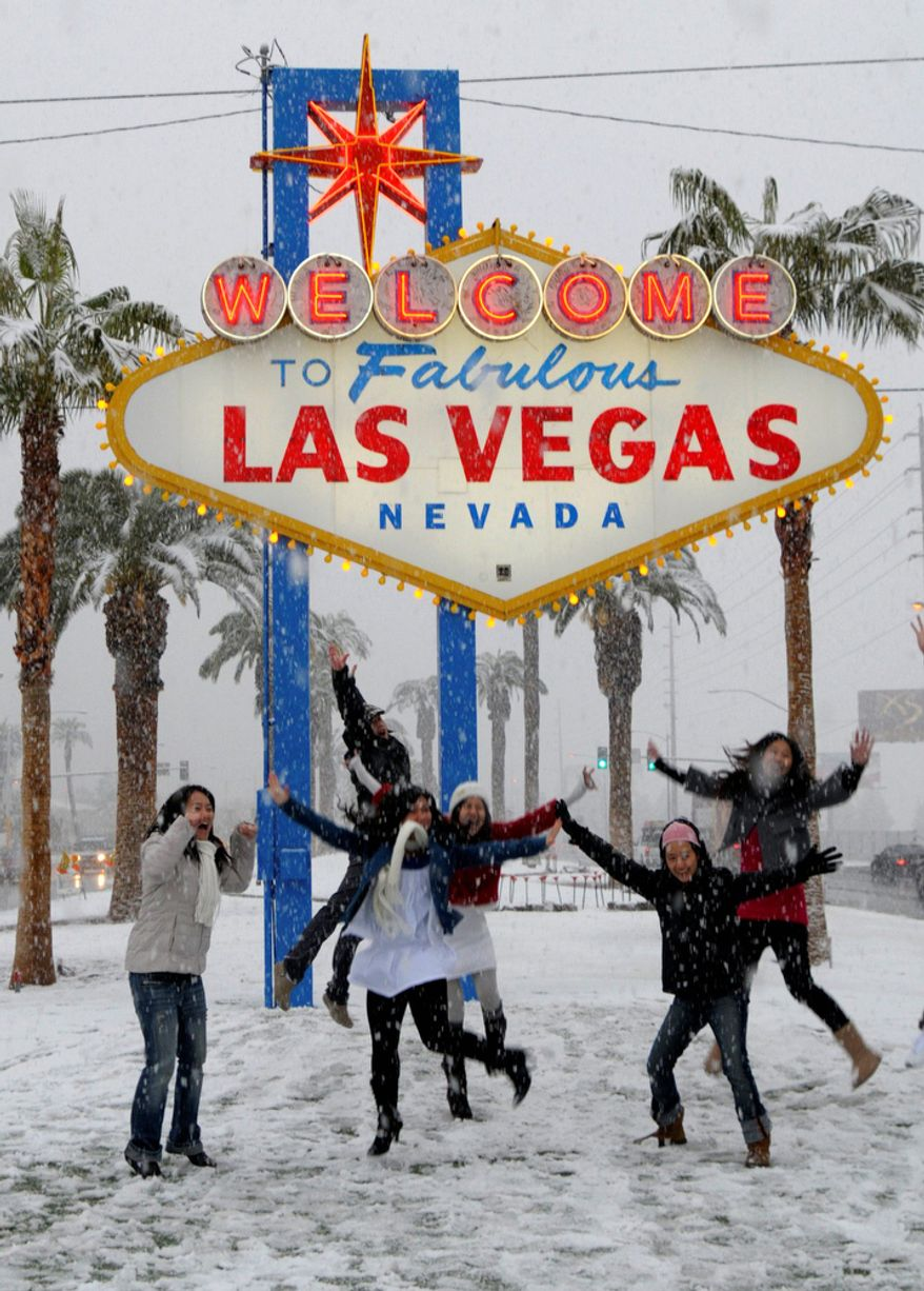 People play in the snow in front of the Las Vegas welcome sign in Las Vegas on Wednesday, Dec. 17, 2008. 
