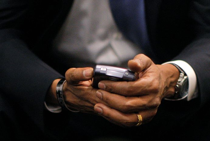 ** FILE ** Then President-elect Barack Obama checks his BlackBerry in St