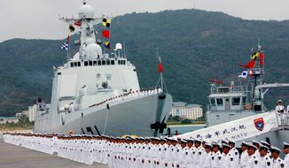 A ceremony is held Friday before a Chinese naval fleet set sail from Sanya city, in China's southernmost island province of Hainan. The warships, carrying special forces, helicopters and armed with guided missiles, were dispatched to Somalia for anti-piracy duty. (Associated Press)