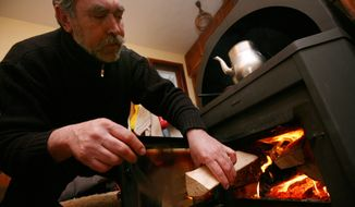 A man loads a wood-burning stove at his home in the town of Elin Pelin near the Bulgarian capital Sofia, Wednesday, Jan. 7, 2009. Bulgaria's energy ministry says Russian gas supplies to Bulgaria, Turkey, Greece and Macedonia have been suspended. Associated Press.