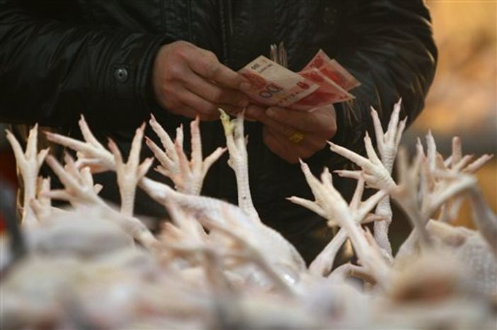 ** FILE ** A customer prepares to pay in a poultry market in Fuyang in central China's Anhui province on Wednesday, Jan. 7, 2009. (Associated Press)