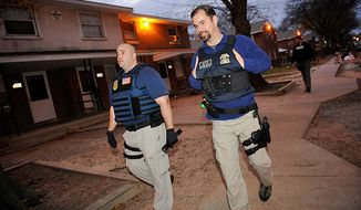 Special agents David Stone (left) and Darrell Bonzano with the Bureau of Alcohol, Tobacco, Firearms and Explosives walk the beat on a street in the Fairfield Court neighborhood of Richmond during a routine patrol of a Violent Crime Impact Team last month. (Barbara L. Salisbury / The Washington Times)