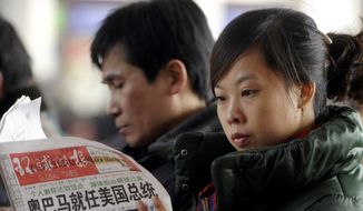"""Agence France-Presse/Getty Images A woman reading a newspaper on Wednesday in Beijing will not find President Obama's entire speech; the state news agency cut a reference to facing down """"fascism and communism."""""""