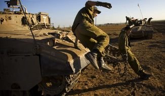 ** FILE ** Israeli soldiers are seen in a staging area near Israel's border with the Gaza Strip, in southern Israel, Tuesday, Jan. 27, 2009. (Associated Press)