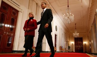 In this 2009 photo, President Obama walks with Lilly Ledbetter to the East Room of the White House where he signed the equal-pay bill into law. (The Washington Times)