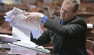 State Senator Jeff Dunham, R- Merced, lifts up a stack of paperwork concerning the stalled state budget that has grown on his desk over the past few days at the Capitol in Sacramento, Calif., Monday, Feb. 16, 2009. Associated Press.
