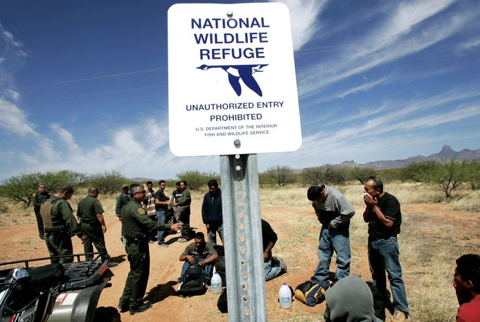 U.S. Border Patrol agents detain a group of men on National Wildlife Refuge land outside of Sasabe, Ariz., in 2006. Environmental concerns have limited the range of patrol agents along the U.S.-Mexico border. (Associated Press)