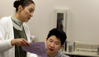 ** FILE ** Korrapong Techaarpornkul (seated) of Los Angeles gets help from Yolanda de la Fuente, an employment specialist who assists students in finding new career opportunities, at the Pasadena City College Career Center in Pasadena, Calif., in March 2009. (Associated Press)