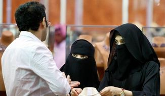 Saudi women look at jewelry at a gold fair last month in Riyadh, Saudi Arabia. Female activists in the religiously conservative kingdom are hoping for more rights in a country where women are segregated from men in nearly all aspects of public life. (Associated Press) ** FILE **