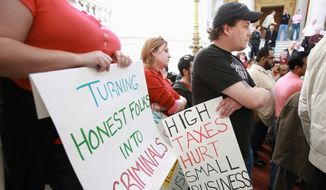 Wholesale cigarette distributor Phil Sealey (right) of Cumberland, R.I., participates in a rally to protest increased cigarette taxes outside the State House in Providence, R.I., March 31. (Associated Press)